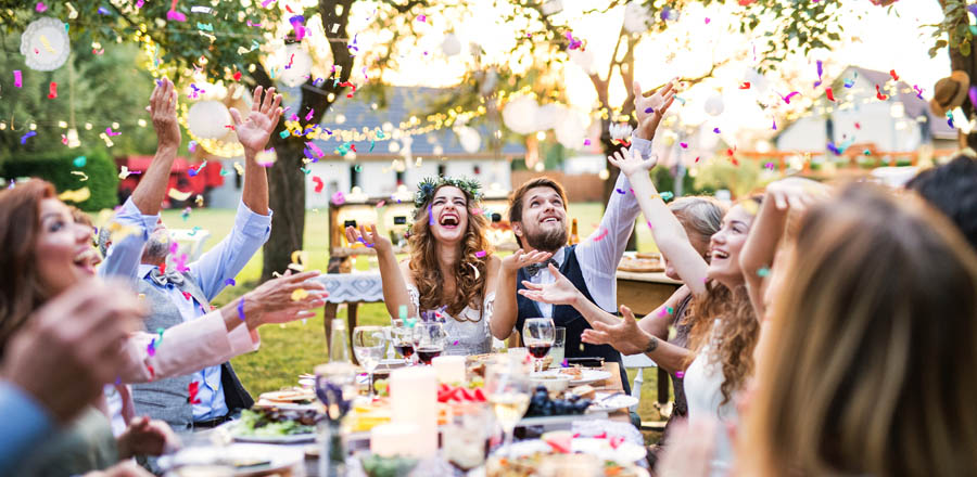 Bride and groom with guests at wedding reception outside in backyard